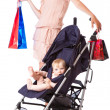 A young woman is standing near her child in a pram — Stockfoto