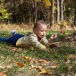 A girl is laying on a grass in the forest - Stock Photo