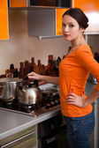 A young woman is putting a kettle — Stock Photo