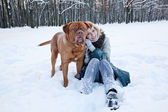 A beautiful woman is sitting near her dog in the winter park — Stock Photo