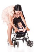 A young woman is standing near her child in a pram — Stock Photo