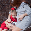 A pregnant woman with her daughter looks at picture on the sofa - Стоковая фотография