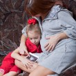 A pregnant woman with her daughter looks at picture on the sofa - Foto Stock
