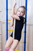 A beautiful girl climbs on a rope — Stock Photo