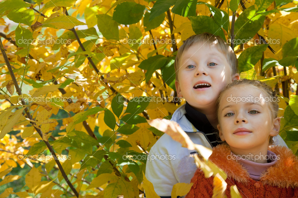 A smiling boy with a cute girl are in the autumn park — Stock Photo #4743276