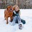 A woman is sitting at the snow with her dog — Stockfoto