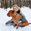 A woman is sitting at the snow with her dog — Stock Photo
