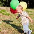 A boy is standing on a lawn with colorful balloons — Stock Photo