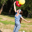 A girl is jumping with colorful baloons — Stock Photo