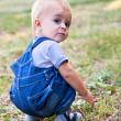 A boy is looking for something in the grass — Stock Photo #4880565