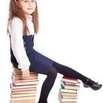 Schoolgirl is sitting on the books — Stock Photo #4881546
