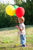 Een jongen is permanent op een grasveld met kleurrijke ballonnen — Stockfoto