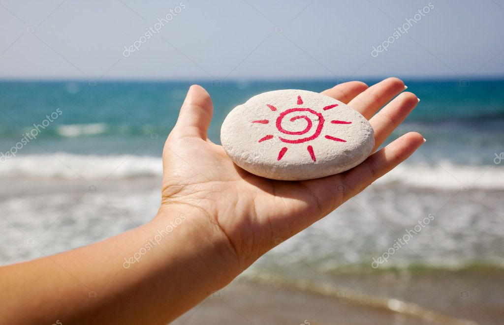 A stone with the image of the sun in a hand of a woman — Stock Photo #4881479