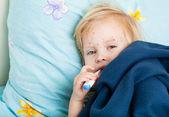 Chory dziewczynka siedzi koło łóżka — Zdjęcie stockowe