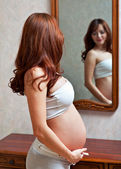 Eine schwangere frau betrachtet sich im spiegel — Stockfoto