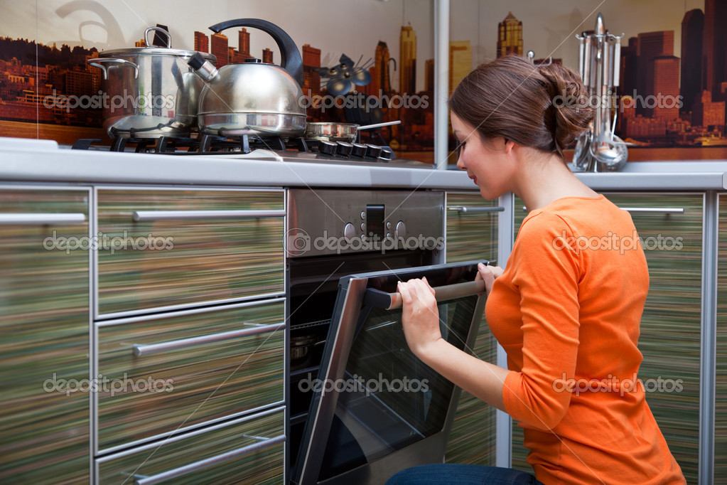 A young beautiful woman is cooking in the stove — Stock Photo #4999863