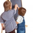 Boys are drawing on a blackboard - Stock Photo