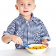 Royalty-Free Stock Photo: A boy is eating cereal from a bowl