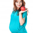 A pregnant smiling woman is holding an apple in her hand - Stock Photo