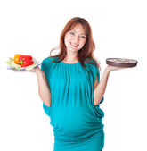 A pregnant smiling woman is holding food in her hands — Stock Photo