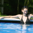 Happy woman in  pool - Stockfoto