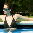 Woman relaxing in the pool — Stock Photo
