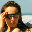 Woman in sunglasses in chaise - Stockfoto