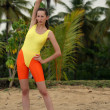 Woman stretches at the beach — Stockfoto