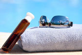Sunglasses, towel and oil bottle — Stock Photo