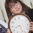 Unhappy woman holding big watch — Stock Photo