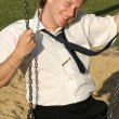 Businessman on a swing — Stock Photo
