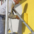 Painter with roller working - Stock Photo