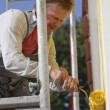 Foto Stock: Worker painting house with roller