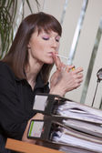 Female smoking in office — Stock Photo