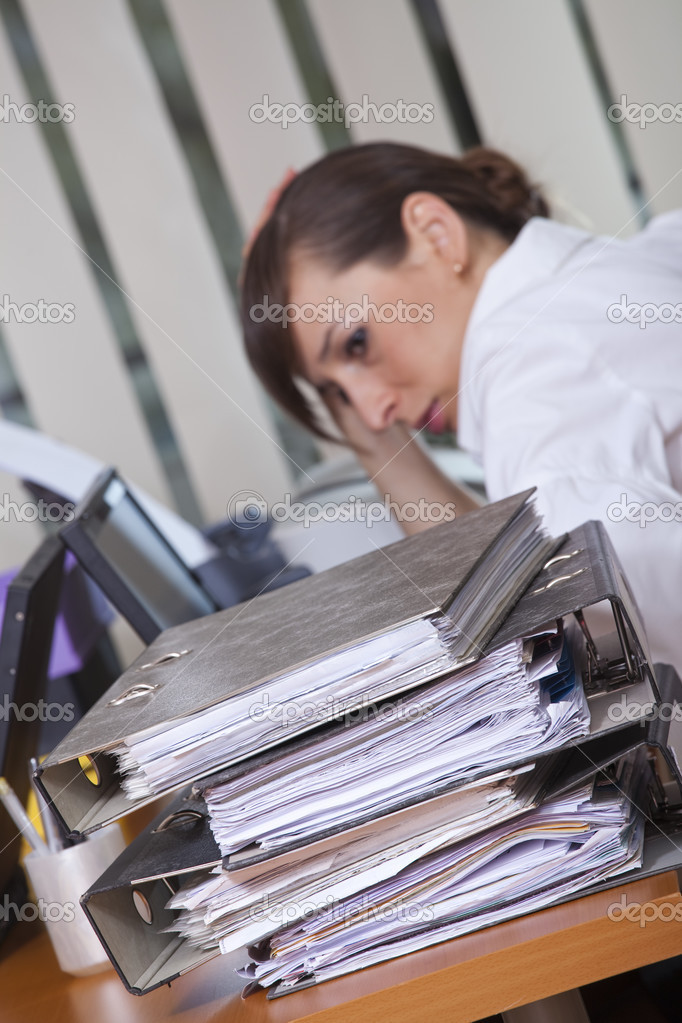 Tired businesswoman sitting at her desk with lots of folders - focus on documents in foreground — Stock Photo #2905403