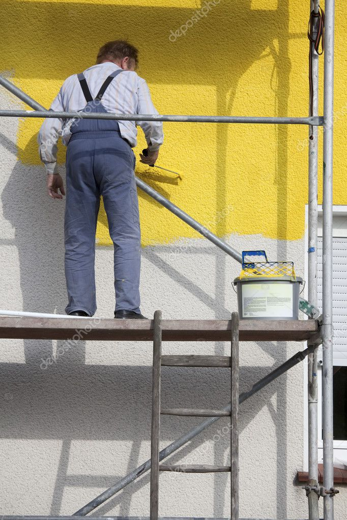 Worker on a scaffold painting house with roller  Foto Stock #2908676