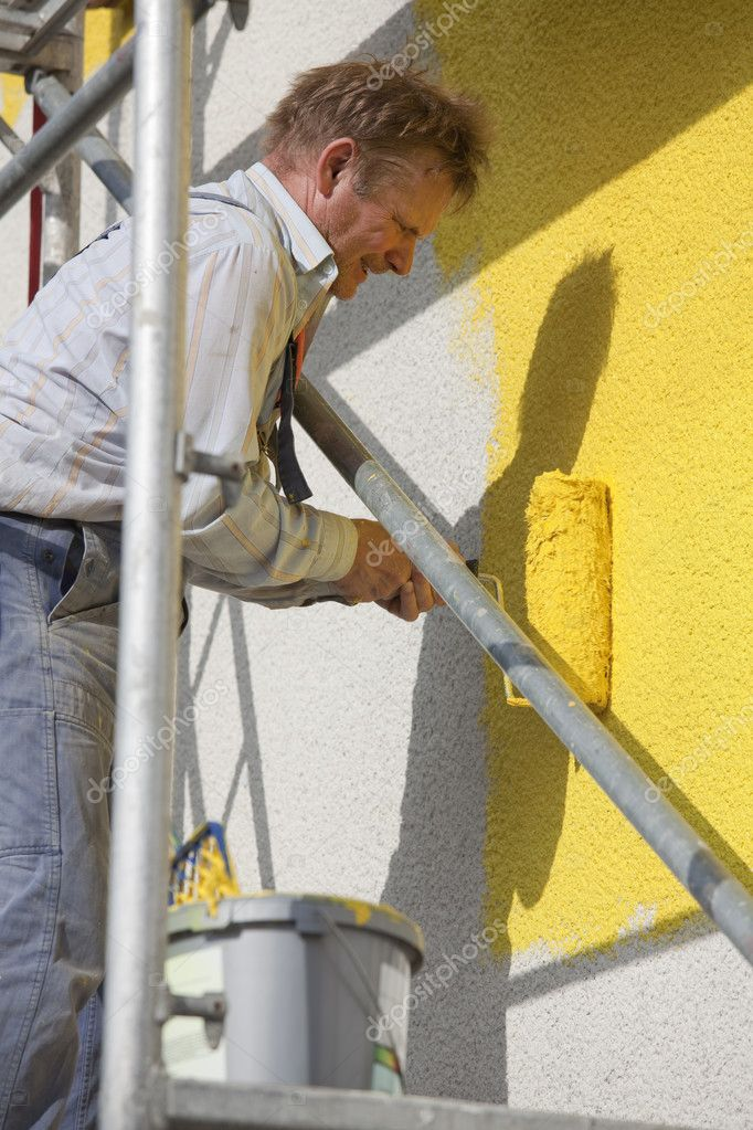 Worker on a scaffold painting house with roller — Stock Photo #2908690