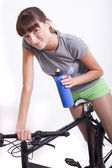 Woman with bottle on bike — Stock Photo