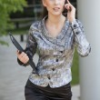 Royalty-Free Stock Photo: Businesswoman walking and talking on cell phone