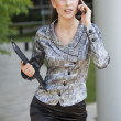 Businesswoman walking and talking on cell phone — Stock Photo