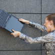 Woman crushing laptop against wall — Stock Photo