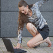 Woman beats laptop with shoe — Stock Photo