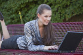 Happy woman with laptop on bench — Stock Photo