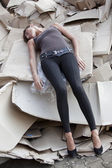 Unconscious woman lying in cartons — Stock Photo