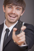 Laughing businessman showing cell phone — Stockfoto