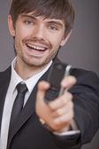Skrattar affärsman visar mobiltelefon — Stockfoto