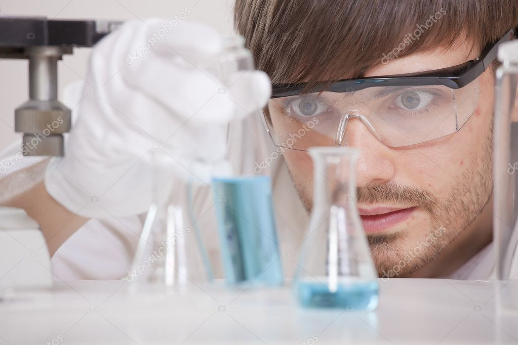 Male scientist in research lab holding glass flask with blue fluid  Photo #3605437