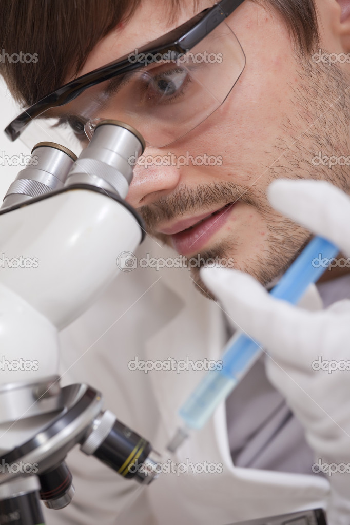 Scientific Research - man looking in microscope with syringe in his hand  Stock Photo #3605448