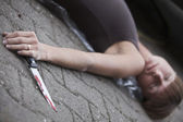 Unconscious woman with knife — Stock Photo