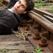 Young man laying on a railway tracks - Stock Photo